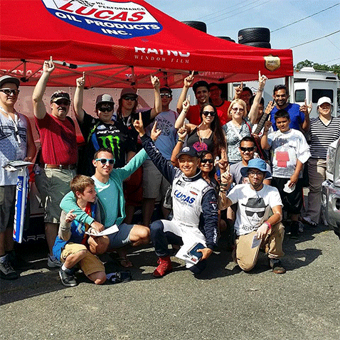 A group of motorsports fans are holding up a winning number one with their index fingers