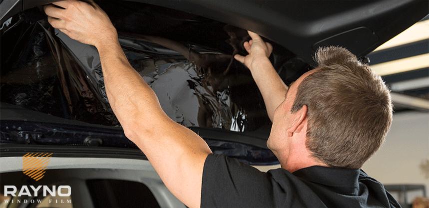 man installing window tint film