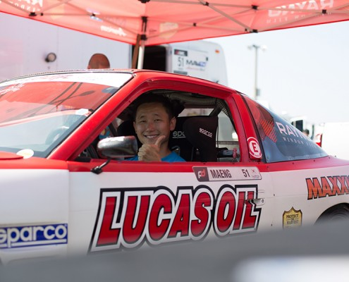 Joon Maeng giving a thumbs-up to the camera in his Rayno sponsored car