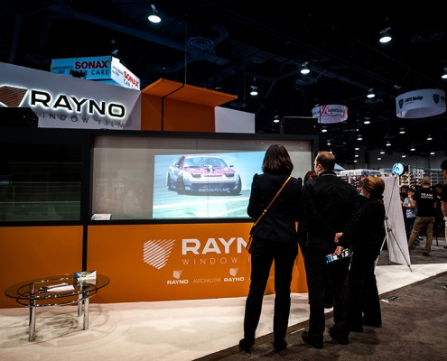 A group of attendees at the 2014 SEMA Show stop to watch a video at the Rayno booth