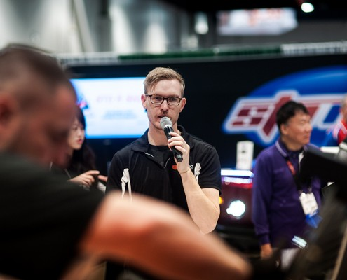 A representative from Rayno Window Film speaking on the microphone at the 2014 SEMA Show